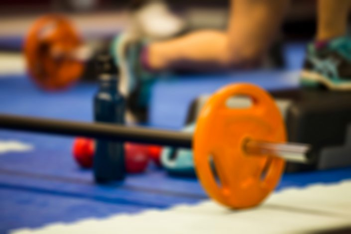Gym equipment on the floor with barbell in focus